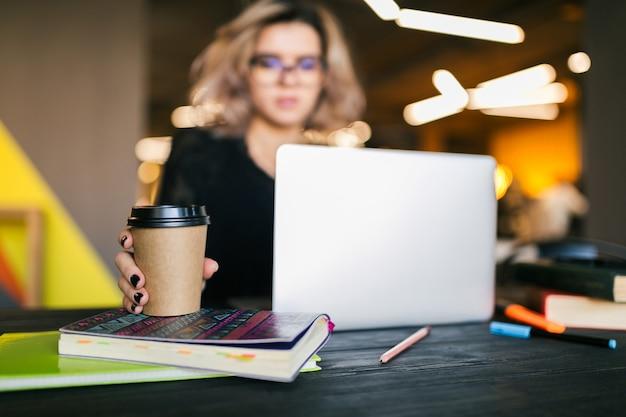 Manos de joven mujer bonita sentada a la mesa en camisa negra trabajando en la computadora portátil en la oficina de co-trabajo, ocupado estudiante independiente, tomando café Foto gratis