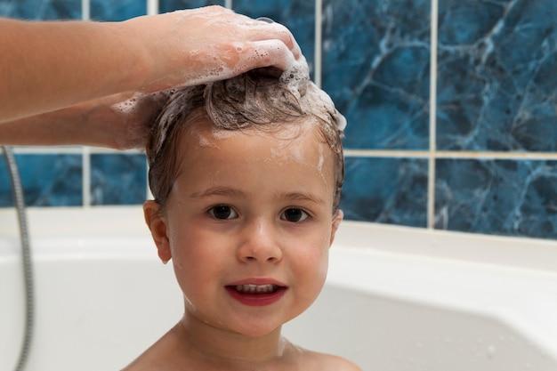 Las manos de mamá lavando la cabeza de la pequeña niña en el baño. Foto Premium