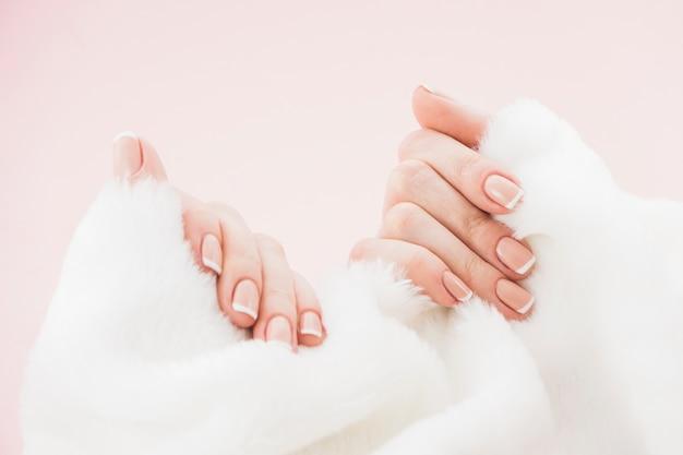 Manos con manicura sosteniendo toalla Foto gratis