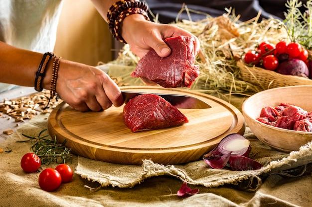 Las manos marrones en pulseras cortan carne fresca Foto Premium