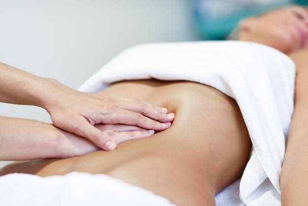 Manos masajear abdomen.therapist femenino aplicar presión sobre el vientre. Foto gratis
