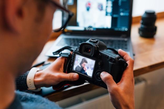 Manos masculinas con cámara profesional, mira fotos, sentado en el café con la computadora portátil. Foto gratis