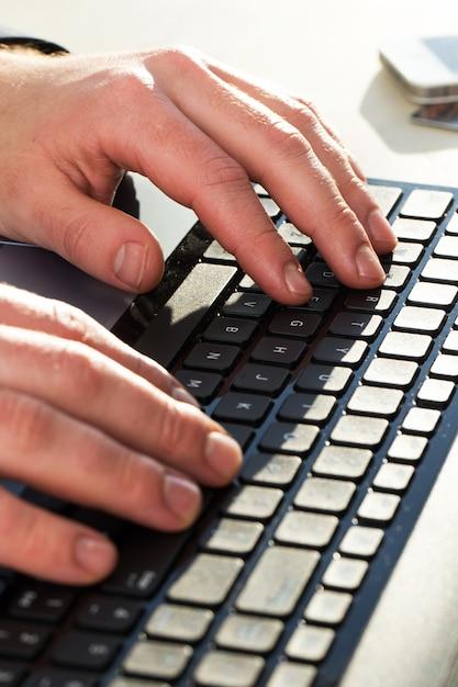 Manos masculinas en teclado Foto gratis
