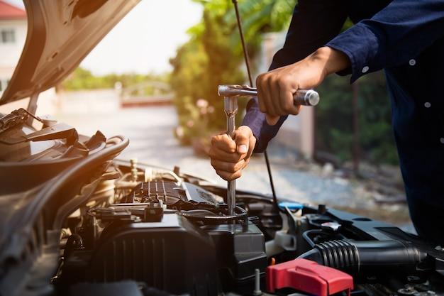 Manos del mecánico de automóviles con llave para reparar el motor de un automóvil. Foto Premium