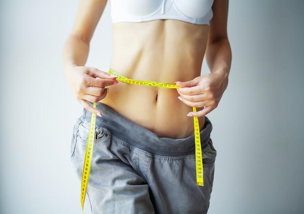 Manos midiendo la cintura con una cinta. mujer delgada y sana en su casa Foto Premium