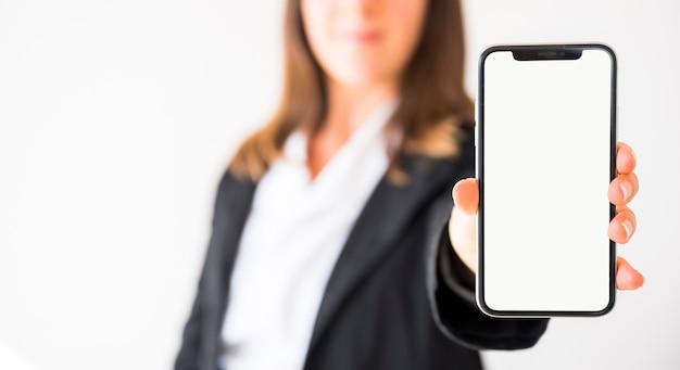 Manos mostrando un teléfono móvil con la pantalla en blanco Foto gratis