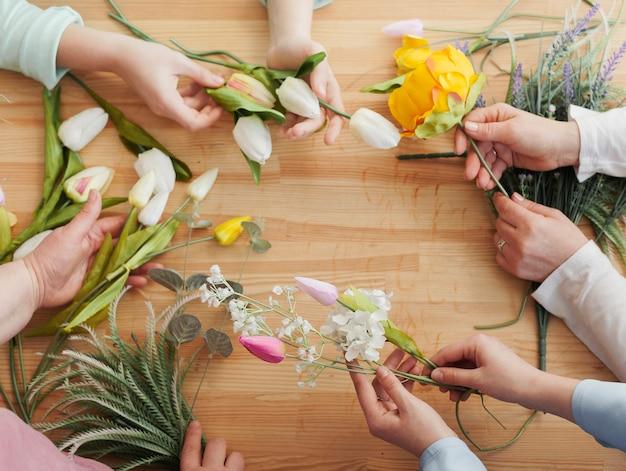 Manos de mujer alta vista con flores de primavera Foto gratis