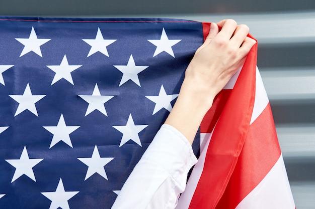 Manos de mujer, colgando la bandera de estados unidos en una pared gris, concepto de día de la independencia de estados unidos Foto Premium