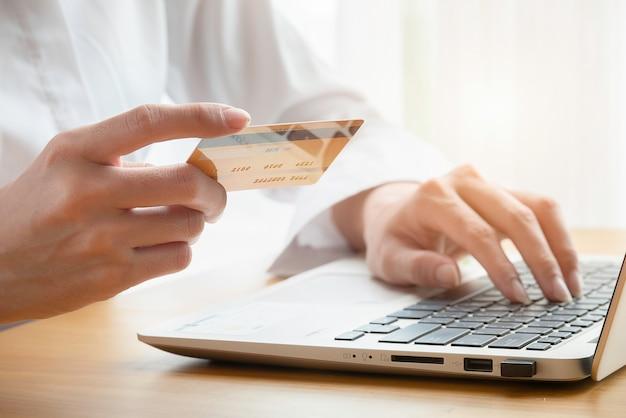 Manos de mujer compran en línea sosteniendo una tarjeta de crédito con una computadora portátil en la mesa Foto Premium