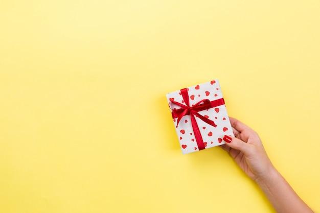 Manos de mujer dan envuelto san valentín en papel con cinta roja. Foto Premium