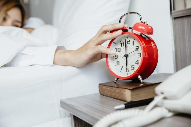 Manos de mujer para detener el despertador Foto Premium