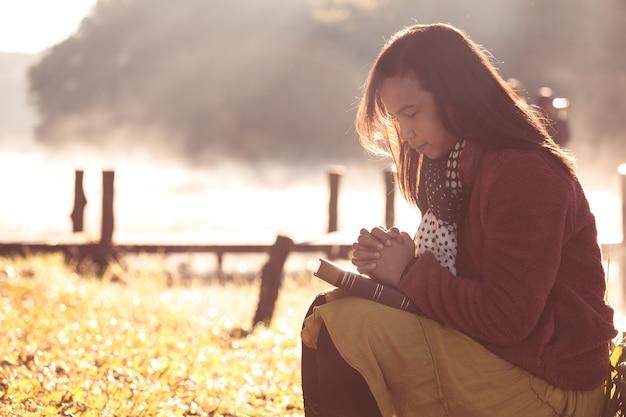 Manos de mujer dobladas en oración en una santa biblia para la fe en el fondo de la hermosa naturaleza Foto Premium