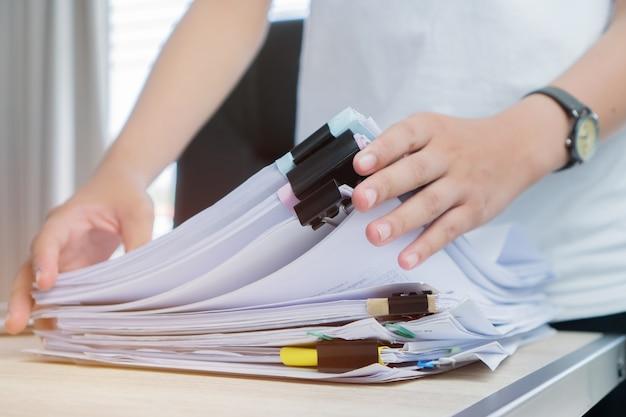 Las manos de la mujer del empleado que trabajan en los archivos de papel de las pilas para buscar la comprobación inacabada