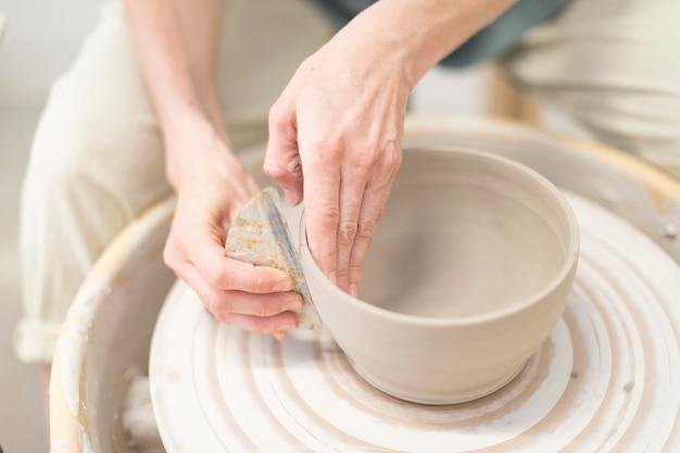 Manos de mujer hace olla de barro en la rueda de alfarería Foto Premium