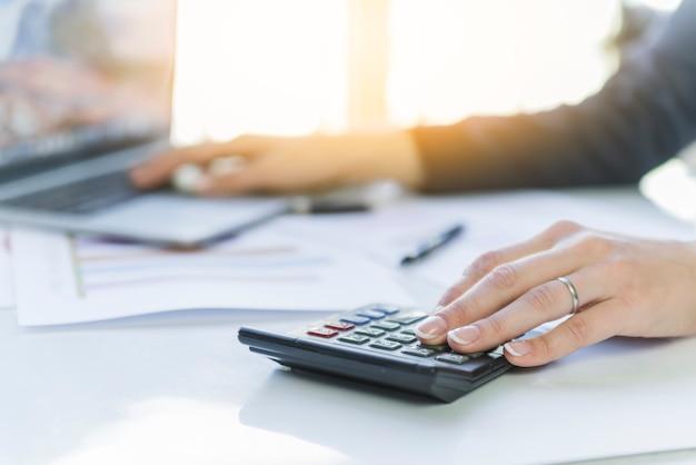 Manos de mujer haciendo cálculos en el lugar de trabajo Foto gratis