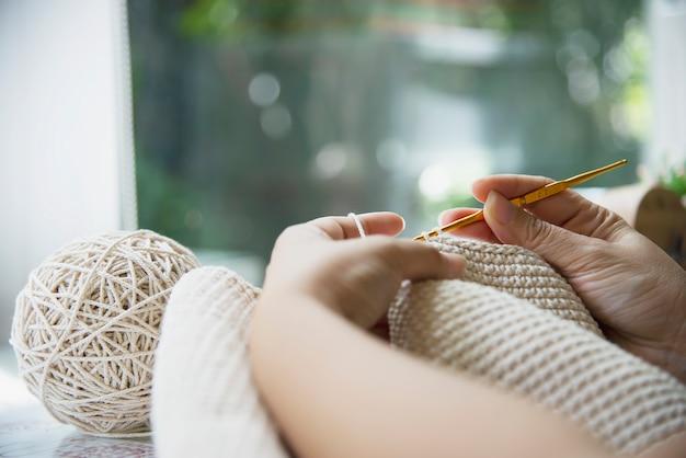 Manos de mujer haciendo trabajo de tejer en casa Foto gratis
