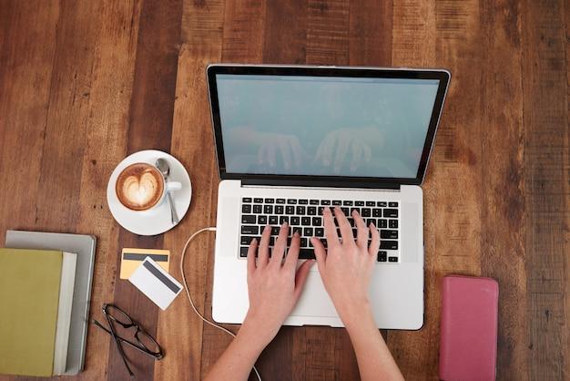 Manos de mujer irreconocible trabajando en la computadora portátil, con capuchino y tarjetas de crédito en la mesa Foto gratis