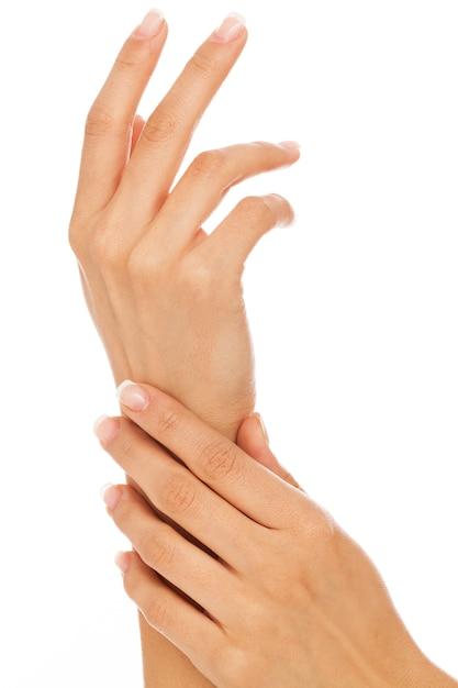 Manos de mujer joven con manicura francesa Foto gratis