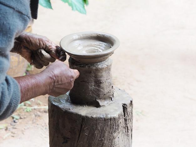 Las manos de la mujer mayor esculpen cerámica de barro sobre soporte de madera. Foto Premium
