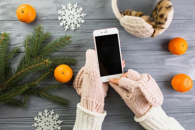 Manos de mujer en mitones con teléfono inteligente cerca de ramas de abeto y copos de nieve de papel Foto gratis