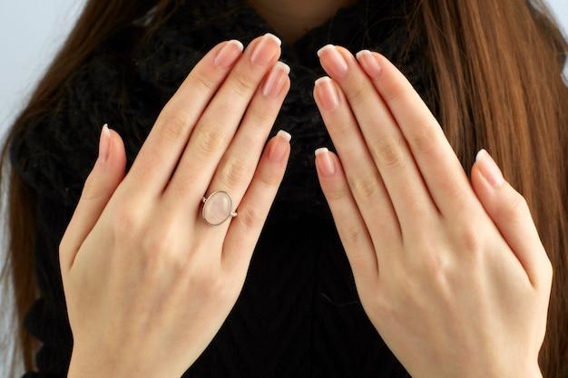 Manos de mujer mostrando un anillo y una hermosa manicura Foto Premium