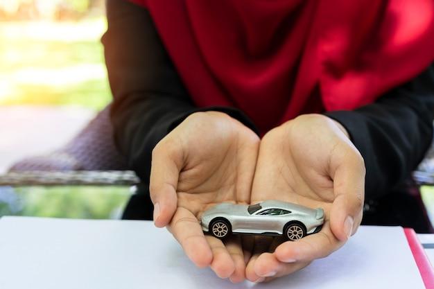 Manos de mujer musulmana de negocios sosteniendo el coche Foto Premium