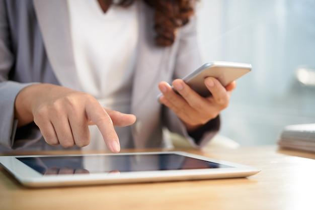 Manos de mujer de negocios anónima con tableta digital y teléfono inteligente en el trabajo Foto gratis