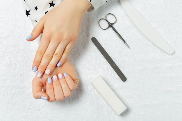 Manos de mujer recibiendo una manicura en un salón de belleza Foto Premium