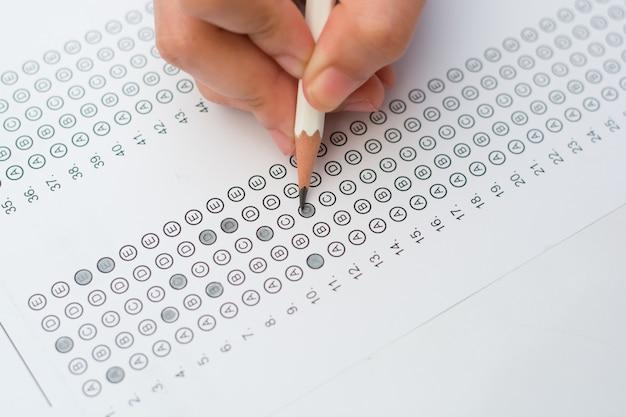 Manos de mujer rellenando formulario de prueba estandarizado. Foto Premium