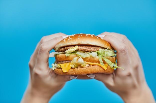 Manos de mujer sosteniendo una hamburguesa en un azul Foto Premium