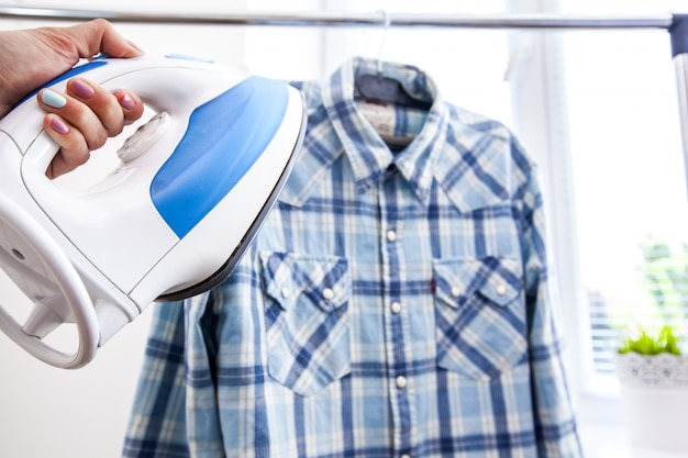 Manos de mujer sosteniendo hierro caliente, ropa humeante Foto Premium