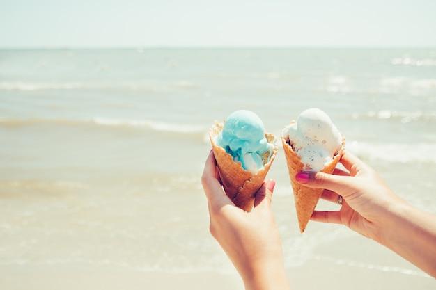 Las manos de la mujer sostiene dos helados en el mar Foto Premium