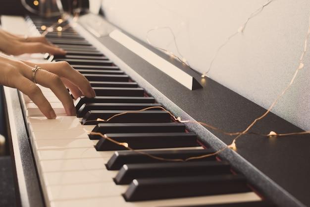 Manos de mujer tocando el piano. fondo del teclado día internacional del jazz. Foto Premium