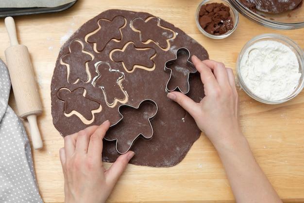Las manos de las mujeres cocinar festivas galletas de jengibre de navidad. cocinar galletas de chocolate o postre. Foto Premium