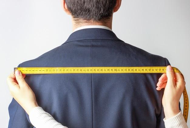 Las manos de las mujeres miden la chaqueta con cinturón santiment en blanco, vista posterior Foto Premium
