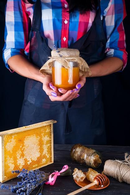 Las manos de las mujeres sostienen un frasco de vidrio con miel orgánica y floral sobre un fondo oscuro Foto Premium