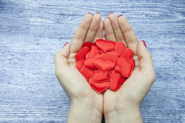 Las manos de las mujeres sostienen muchos corazones rojos en la palma contra el fondo de madera del color de los jeans, el concepto de salvar el amor Foto Premium