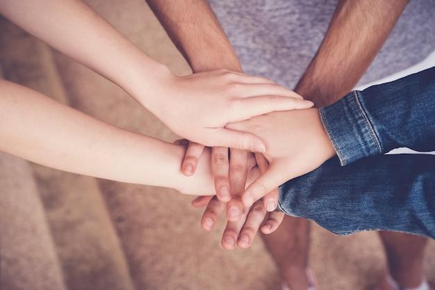 Manos multiétnicas de jóvenes adultos juntando las manos, concepto de trabajo en equipo de voluntarios y caridad Foto Premium