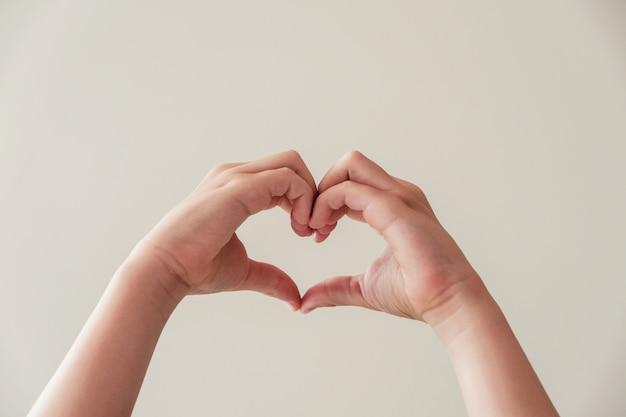 Manos del niño haciendo forma de corazón, salud del corazón, donación, caridad voluntaria feliz Foto Premium