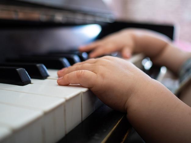 Manos de un niño pequeño tocando las teclas del piano Foto Premium