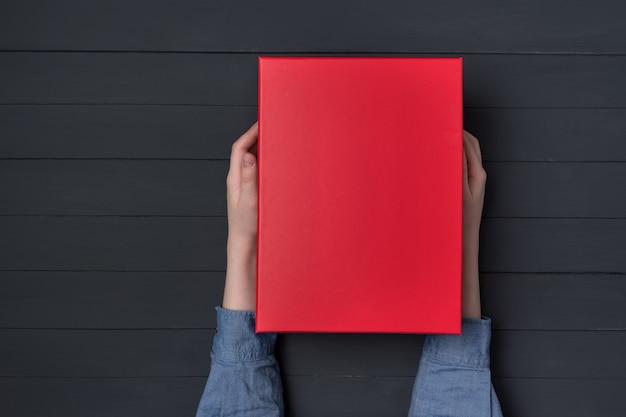 Las manos de los niños tienen una caja de regalo roja. fondo negro. Foto Premium
