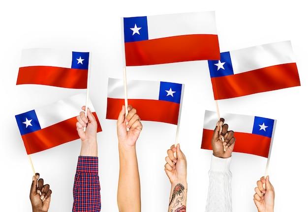 Manos ondeando banderas de chile Foto gratis