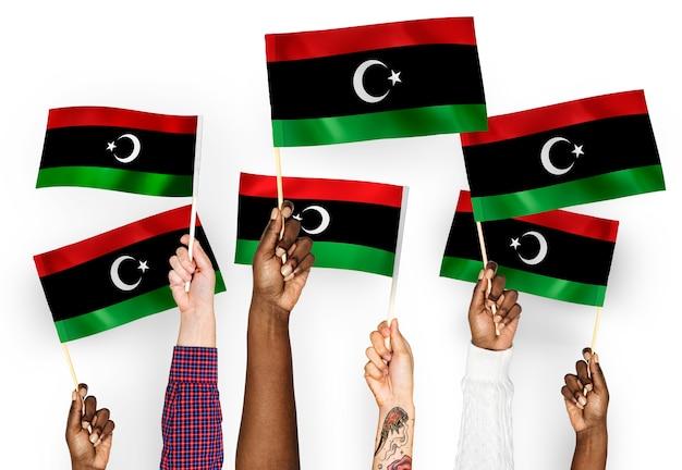 Manos ondeando banderas de libia Foto gratis