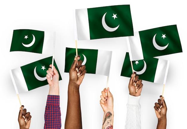 Manos ondeando banderas de pakistán Foto gratis