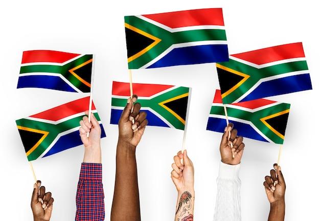 Manos ondeando banderas de sudáfrica Foto gratis