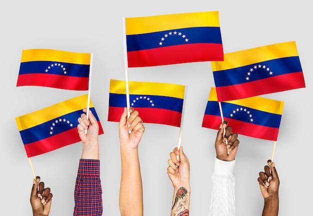 Manos ondeando banderas de venezuela Foto gratis