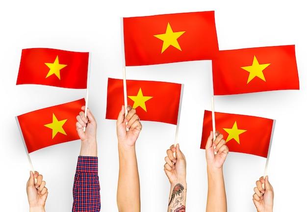 Manos ondeando banderas de vietnam Foto gratis