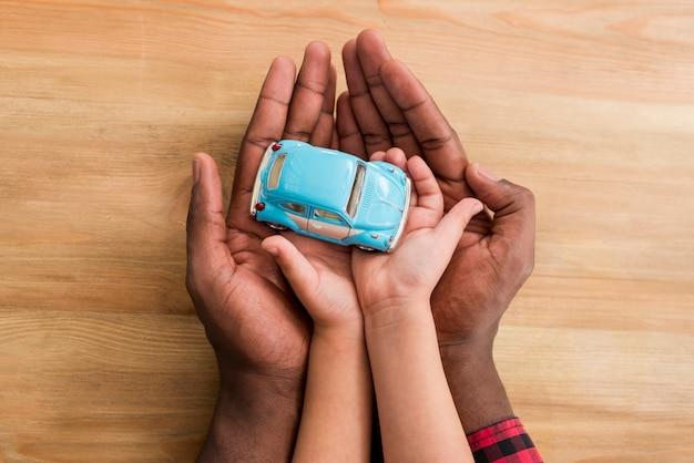 Manos de padre e hijo con carro de juguete Foto gratis