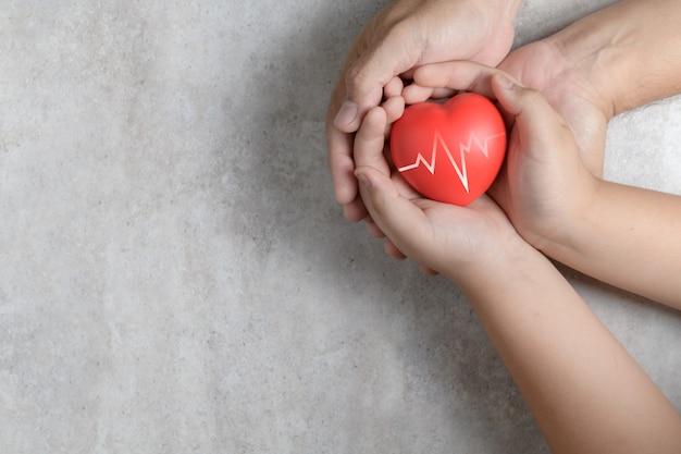 Manos del padre y del niño que llevan a cabo el corazón rojo en el mármol Foto Premium