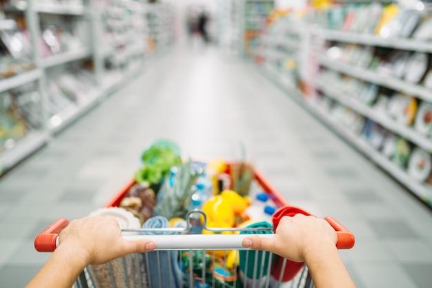 Las manos de la persona femenina arrastra el carro lleno de mercancías en un supermercado, de compras. cliente en la tienda, comprador en el mercado, concepto de compras Foto Premium